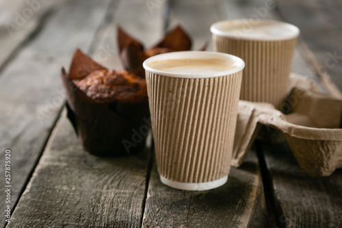 Fototapeta Coffee to go with muffin on wood background, copy space