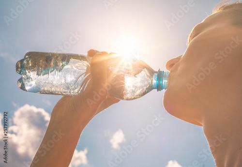 Valokuvatapetti Young woman drinking bottle of water