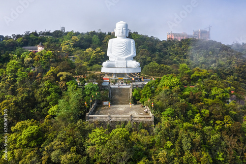 Fototapeta Aerial view of Linh Ung Pagoda with a giant buddha statue among green trees on t