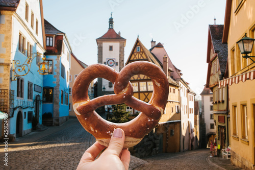 Fotografija The girl holds in her hand a traditional German pretzel on the background of Bavarian architecture in Rottenburg ob der Tauber in Germany