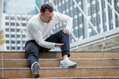 fitness man have knee pain sitting on steps of stair in the city Fototapete