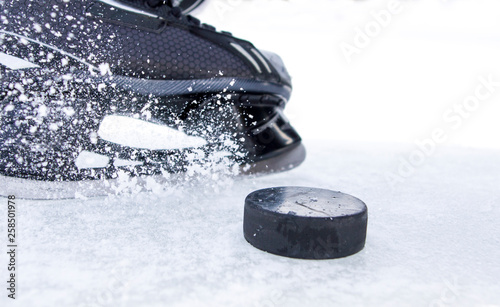 Photo hockey skate with snow splashes and puck