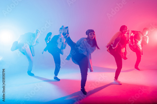 Canvas Print Group of diverse young hip-hop dancers in studio with special lighting effects i