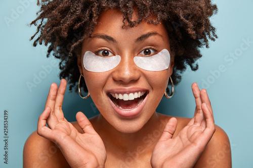Obraz na płótnie Headshot of ovejoyed beautiful woman reduces under eye puffiness, dark circles,