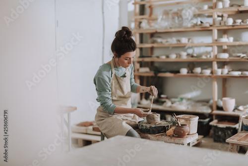 Vászonkép Female ceramic artist in apron working in pottery workshop