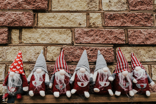 Photo Seven gnomes, dwarfs seating against brick wall.