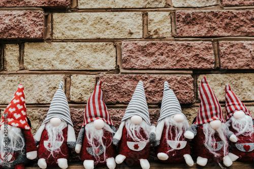 Canvas Print Seven gnomes, dwarfs seating against brick wall.
