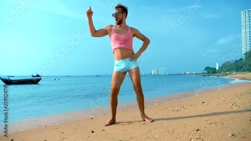 Photo Playful handsome guy in a pink t-shirt and blue shorts rejoices at the beach