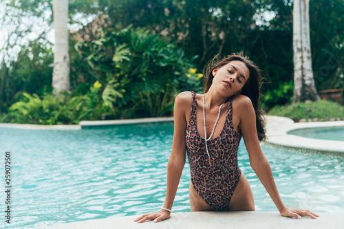 Photo Sexy girl in leopard coloring swimwear resting near swimming pool