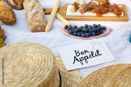 Vászonkép straw hats lay on a white picnic blanket next to nameplate bon apetit bright summer day background