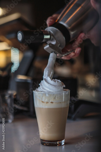 Fototapeta the process of preparing a delicious coffee drink with whipped cream that is dec