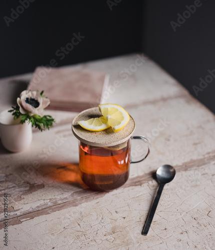 Tee mit Zitrone auf einem Tisch mit Blumen und kleinem Buch