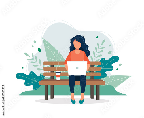 Fotografering Woman with laptop sitting on the bench in nature and leaves