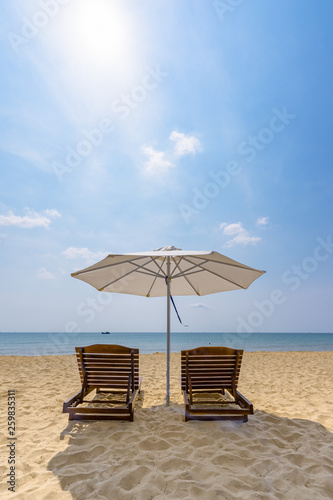 Tablou Canvas Wooden sunbeds and umbrella on the golden sand of a paradise beach