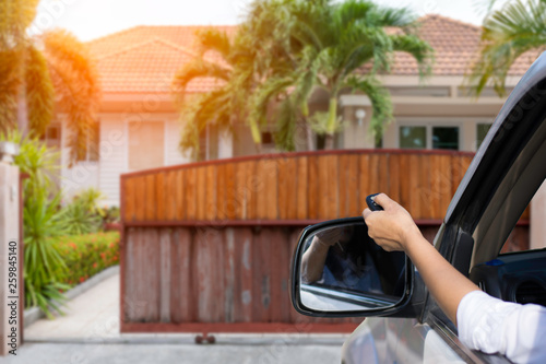 Cuadros en Lienzo Woman in car, hand using remote control to open auto wooden door with modern home blurred background