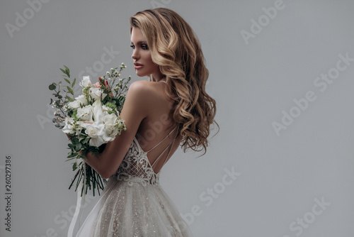 Fotografia beautiful sexy blonde bride posing in a sparkling wedding dress with bouquet