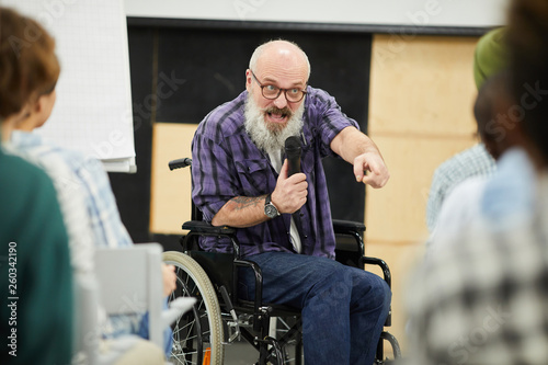 Emotional confident motivational disabled speaker with gray beard sitting in wheelchair and pointing at person in audience while helping students to believe in themselves at conference Fototapete