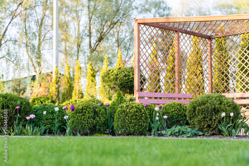 Canvas Print Beautiful green garden with frsesh boxwood bushes, flowers and wood grating summerhouse