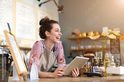 Fotografia Young woman using digital tablet in coffee shop