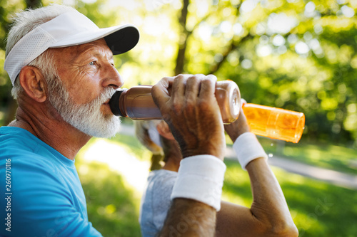 Photographie Hydrating. Sporty senior person drinking water in a park