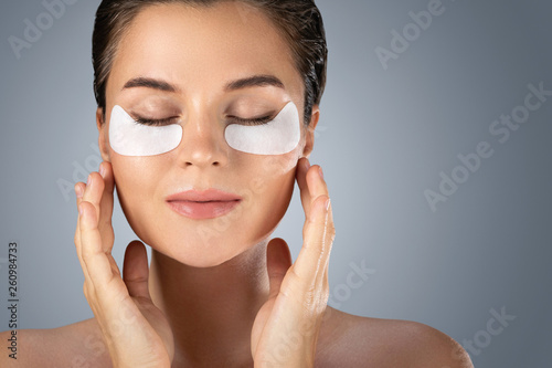 Woman with hydrating eye patches under her eyes o Fototapeta