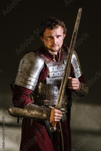 Medieval man knight in armor and weapon on dark background Tapéta, Fotótapéta