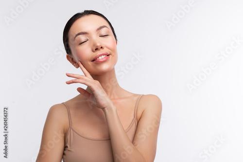 Obraz na plátne Dark-haired woman wearing beige camisole closing her eyes