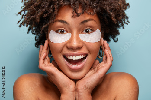 Pure beautiful woman takes care of skin, has under eye patches, keeps hands on face, smiles broadly, has white teeth, Afro haircut, models over blue background Fototapeta
