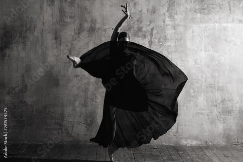 Ballerina in ballroom. Ballet dancer in studio. Black and white monochrome.