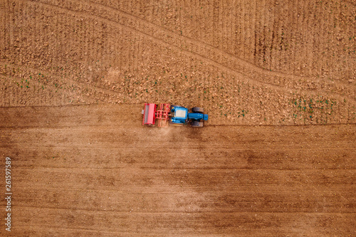 Photo Agriculture tractor plows field of land for sowing