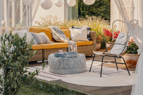 Wallpaper Mural Real photo of an armchair, pouf as a table and wicker couch on a terrace