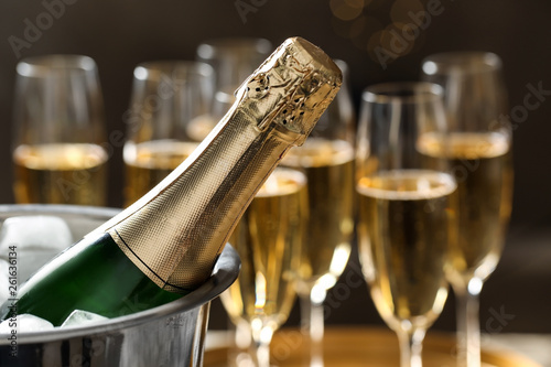 Photo Bottle of champagne in bucket with ice and glasses on blurred background, closeup