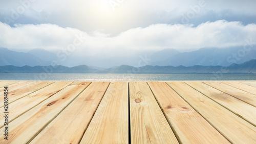 Fotografija Wooden floor platform and lake with sky background
