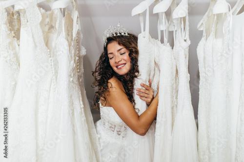 Valokuvatapetti Beautiful young brunette woman choosing wedding dress in a bridal salon