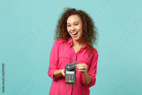 Fotografia Laughing african girl hold wireless modern bank payment terminal to process, acquire credit card payments isolated on blue turquoise background