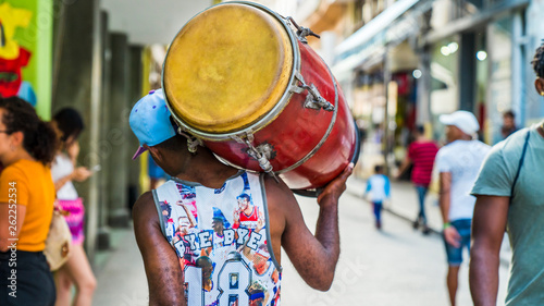 Havana, Cuba. Man walks down the street carrying his drum on his shoulder. Street drummer.