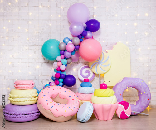 Fotografia set of huge artificial sweets and pastry decorations over white brick wall