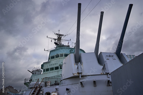Carta da parati Front main gun turret with tree big guns and with captain bridge behing in the british cruiser HMS Belfast who served in World war two in north atlantic ocean and now is exhibited like museum ship