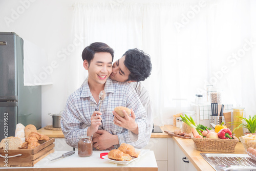 Canvas Print Young asian male homosexual couple wearing pajamas having beakfast in kitchen