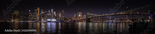 Photo A large panoramic nighttime view of Manhattan and the Brooklyn Bridge from the o