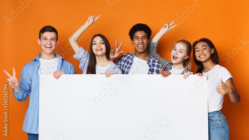 Fotografija Happy friends holding empty banner, orange background
