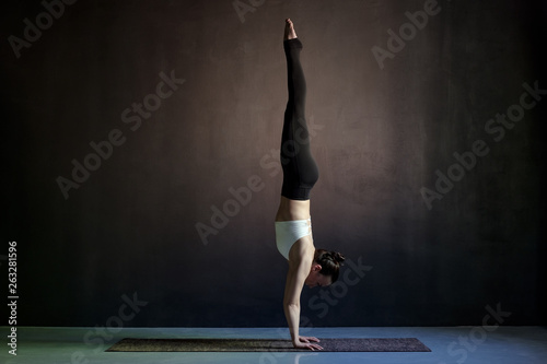 Fotografiet woman practicing yoga, Adho Mukha Vrksasana exercise, Downward facing Tree pose