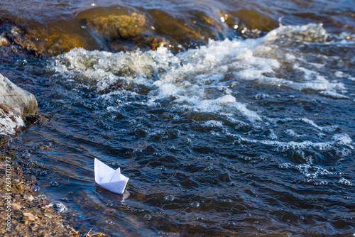 Fotografija A paper boat on a turbulent stream of water struggles with the flow