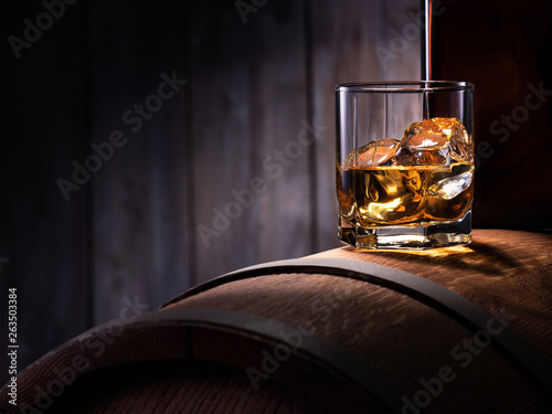 Carta da parati Glass of whiskey with ice cubes on the wooden barrel with wooden background