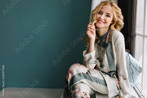 Beautiful young woman with long blonde wavy hair sitting on window sill in room with turquoise wall Fototapete