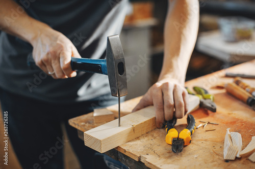 A man carves a tree. The carpenter works with hammer in a studio. An engineer provides a tree shape