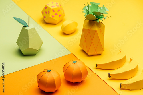 various handmade colorful origami fruits on green, yellow and orange paper
