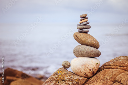 Foto Balance, relaxation and wellness: Stone cairn outside, ocean in the blurry backg