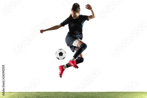 Fotografia Female soccer player kicking ball isolated over white background