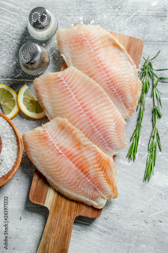 Canvas Print Fish fillet on a wooden cutting Board with rosemary, spices and lemon slices